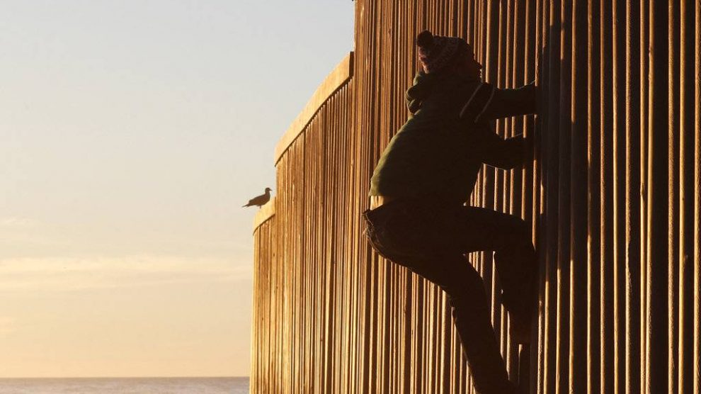 Migrantes en muro fronterizo