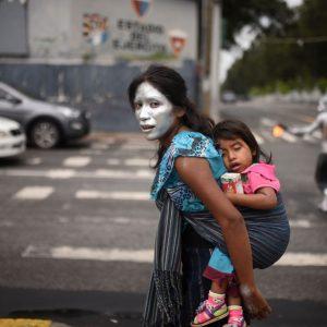 Mujer trabajando en la calle con su niña