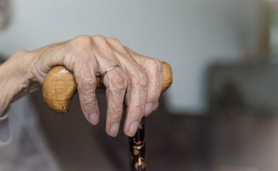 Adulto mayor sostiene un bordón